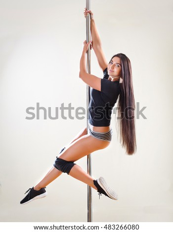 Beautiful woman performing pole dance. Shot with lightbackground.