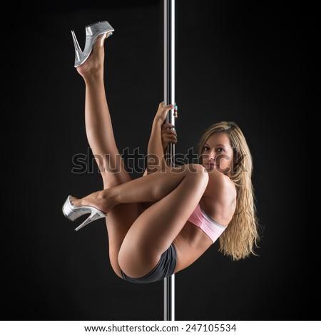 Beautiful woman performing pole dance. Studio shot on black background. - stock photo