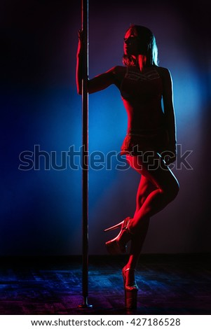Beautiful woman performing pole dance. Studio shot, on colored background. silhouette