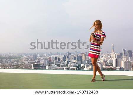 Beautiful woman photographer on the roof of a skyscraper in travel - stock photo