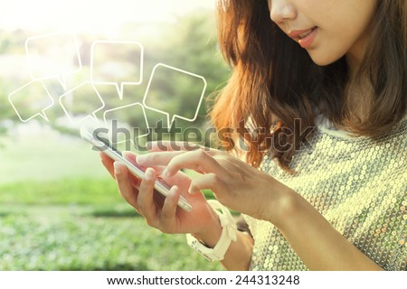 beautiful woman playing and touching on smart phone screen in outdoor of home garden field - stock photo