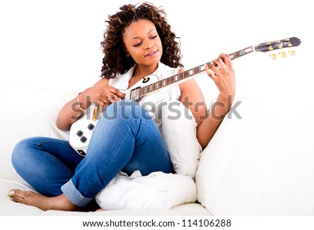 Beautiful woman playing guitar and relaxing at home - stock photo