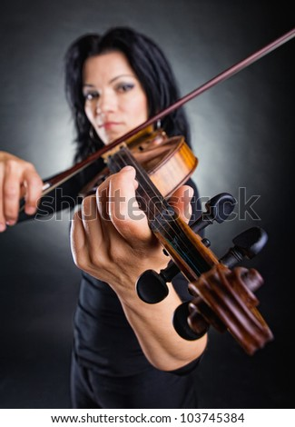 Beautiful woman playing the violin on dark background. Violin in focus - stock photo