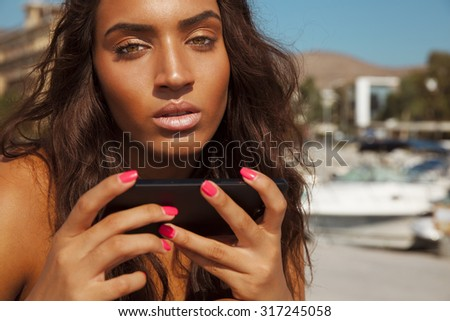 beautiful woman playing with her smart phone. Copyspace for your text. Beauty and technology. horizontal outdoors shot. - stock photo