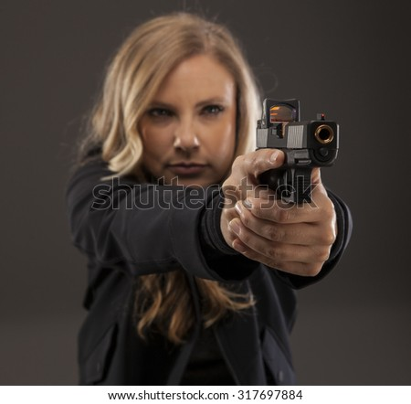 Beautiful woman pointing a gun. REFUSE TO BE A VICTIM. - stock photo