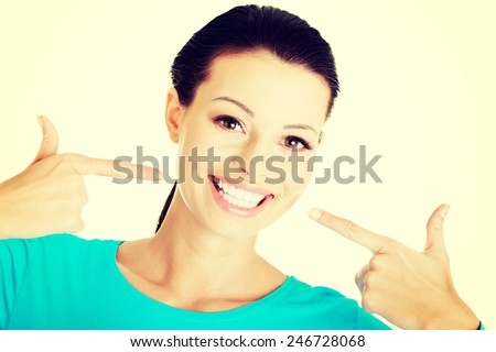Beautiful woman pointing on her perfect white teeth. - stock photo