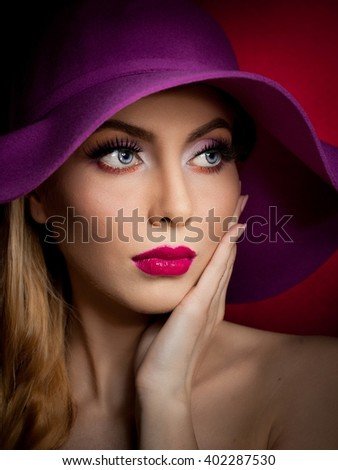 Beautiful woman portrait. Fashion art photo. Beautiful young model with mauve hat on colored background, studio shot. Elegant blonde with makeup. Romantic retro style lady with sensual mouth  - stock photo