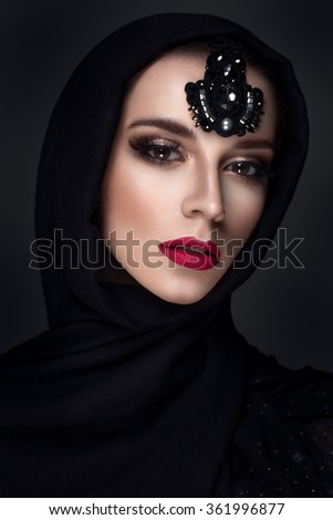 Beautiful woman portrait in east style with headscarf and jewelry on face