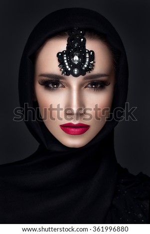 Beautiful woman portrait in east style with headscarf and jewelry on face - stock photo