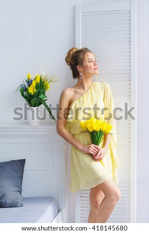 Beautiful woman portrait in fashion yellow dress with bunch of spring tulip flowers - stock photo
