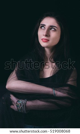 Beautiful woman portrait in low key technique on the dark background