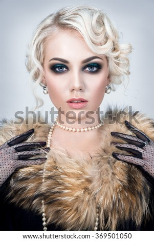 Beautiful woman portrait in retro style with fur and pearls on neck - stock photo