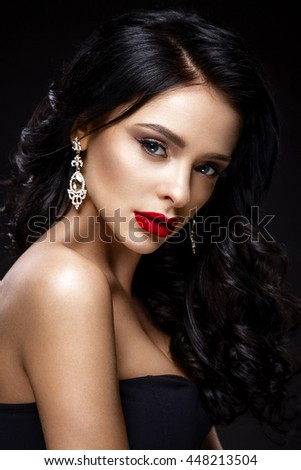 Beautiful woman portrait isolated on black background. Young lady posing with elegant hairstyle, gorgeous make up and red lips.