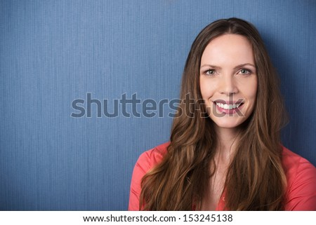 Beautiful woman portrait of a smiling young woman with long brunette hair standing against a dark blue grey background with copyspace - stock photo
