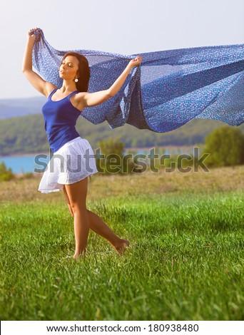 Beautiful woman portrait on the field near the lake - stock photo