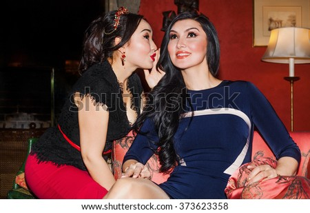 Beautiful woman portrait whispering secrets to her friend in parlor