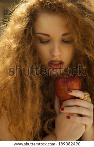 Beautiful woman portrait with an apple. Blonde woman with bright make up and red lipstick. vertical shot, studio - stock photo