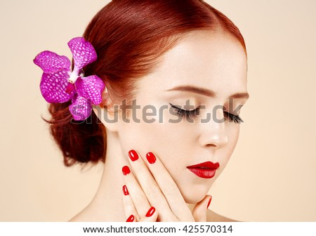 Beautiful woman portrait with flower in hair perfect make up manicure red lips and nails on Beautiful woman portrait with flower in hair perfect make up manicure red lips and nails beige background  - stock photo