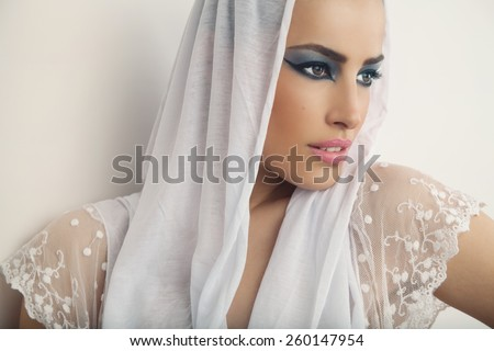 beautiful woman portrait with seductive makeup and white veil over her head, studio white - stock photo