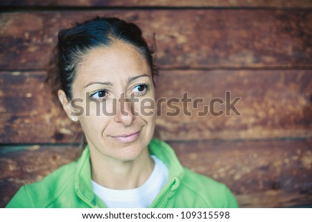 Beautiful woman portrait with wood wall as background. - stock photo