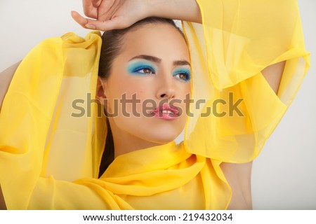 beautiful woman portrait with yellow scarf and stylish blue makeup, studio - stock photo