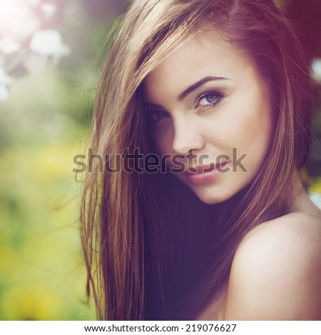 Beautiful woman portrait. Young cheerful girl with long brown hair and clean skin. Outdoor close up portrait