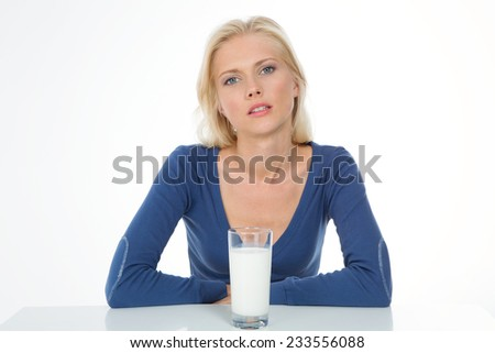 beautiful woman poses in front of glass of white milk - stock photo