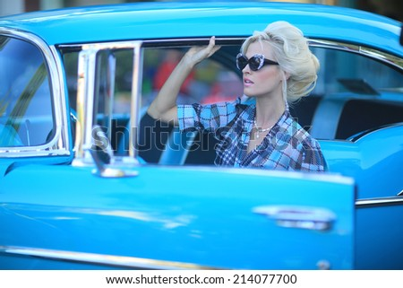 Beautiful Woman Posing and and Around a Vintage Car - stock photo
