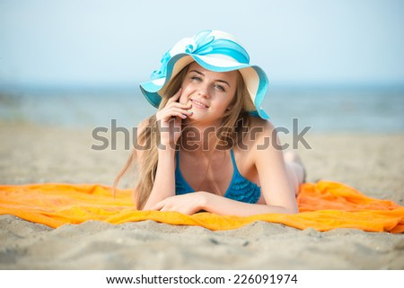 Beautiful woman posing at the summer sand beach. Outdoor summer portrait of pretty sport style woman in blue bikini. Ocean sea coast. Beautiful fit tan girl. slim model caucasian ethnicity outdoors. - stock photo