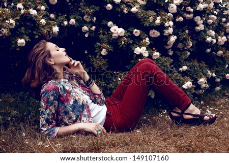 Beautiful woman posing behind rose bush. Botanical garden, outdoor fashion shot - stock photo