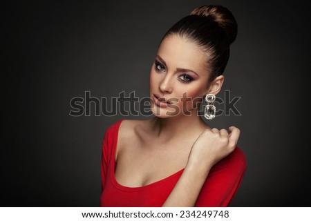 Beautiful woman posing in studio on dark background - stock photo