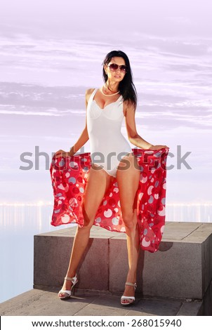 beautiful woman posing in white bathing suit on beach - stock photo