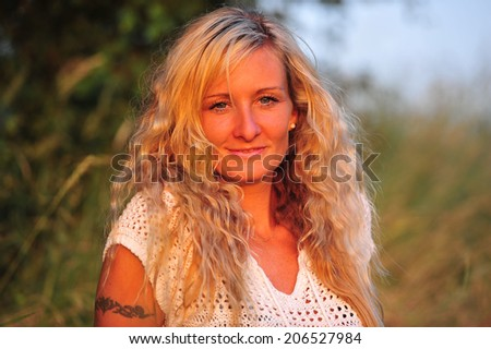 beautiful woman posing on a meadow in the twilight - stock photo