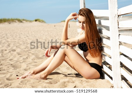 Beautiful woman posing on a paradise beach. Pretty girl on beach. Picture of happy woman with wind surf on the beach.
