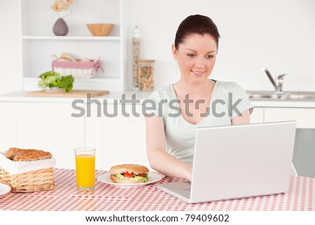 Beautiful woman posing while relaxing with her laptop at lunch time in her kitchen