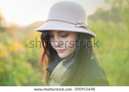 Beautiful woman posing with a hat looking down. Autumn and spring portrait of beauty female model. Close up of caucasian young girl. Elegance lady in nature