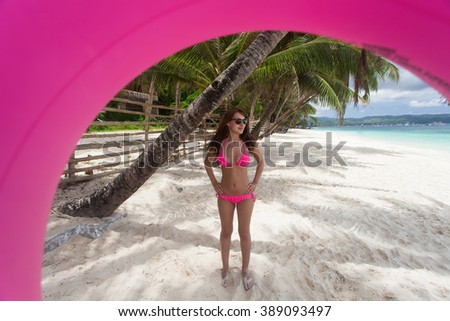 Beautiful woman posing with float tube on the beach