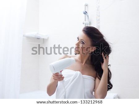 Beautiful woman posing with hairdryer in bathroom