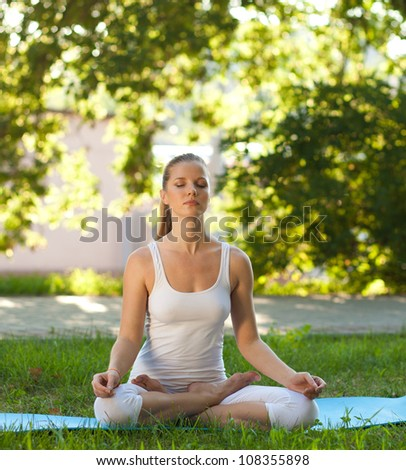 Beautiful woman practices yoga in nature. Lotus Pose, eyes closed - stock photo