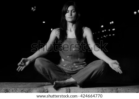 Beautiful woman practicing meditation (Radja Yoga) at night in the city. Mindfulness / calm concept. - stock photo