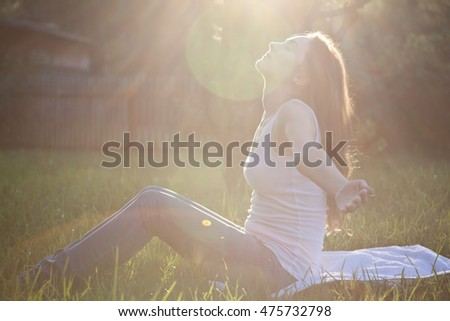 Beautiful woman practicing yoga at the park
