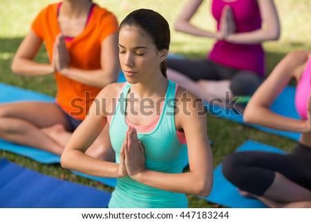Beautiful woman practicing yoga in park - stock photo