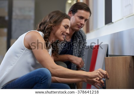 Beautiful woman pulls out her favourite cabinet finish and shows her husband while they shop around the kitchen showroom - stock photo