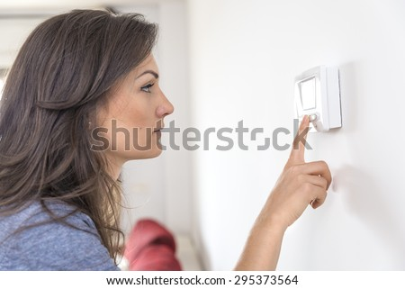 Beautiful woman push button digital thermostat at house