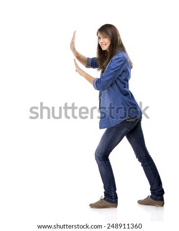 Beautiful woman push something over a white background - stock photo