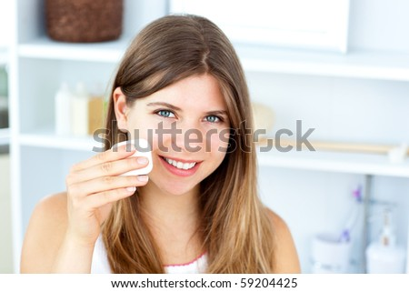 Beautiful woman putting make-up on her face looking at the camera in the bathroom