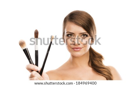 Beautiful woman putting make up on herself and holding make up brushes, isolated on white - stock photo