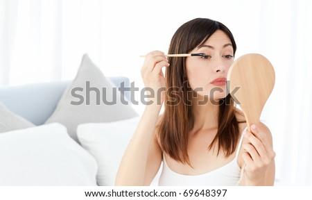 Beautiful woman putting on Make up - stock photo