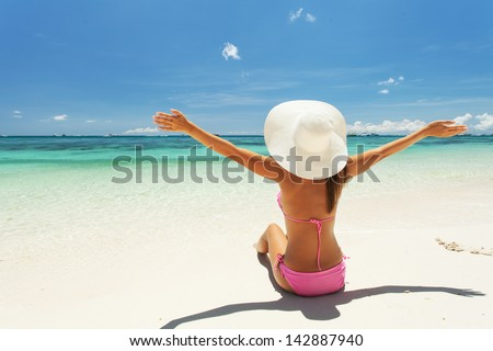 Beautiful woman raised her hands at the beach - stock photo