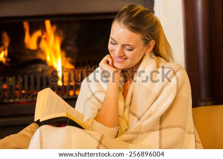 beautiful woman reading a book by fireplace - stock photo